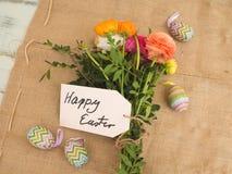 Mensagem easter feliz em telas com um bouchet das flores Fotografia de Stock