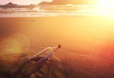 Mensagem em um vidro de garrafa arrolhado na praia do oceano no por do sol dourado conceptual fotos de stock royalty free