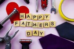 Mensagem feliz do dia de pais em um fundo cor-de-rosa liso com quadro das ferramentas e dos laços imagens de stock royalty free
