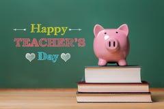 Mensagem feliz do dia dos professores com mealheiro cor-de-rosa Fotos de Stock Royalty Free