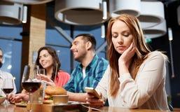 Mensagem furada da mulher no smartphone no restaurante foto de stock