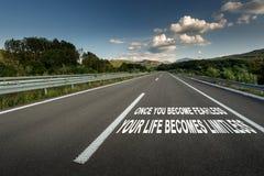 Mensagem inspirador na estrada da estrada do asfalto através do campo imagens de stock