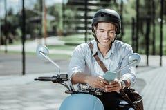 Mensagem jovial alegre da leitura do indivíduo no velomotor fotografia de stock