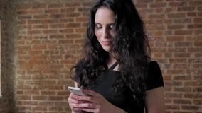 Mensagem moreno bonita nova da leitura da menina, conceito da emoção, conceito de uma comunicação, backgroung do tijolo vídeos de arquivo