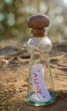 Mensagem na garrafa de vidro na areia com fundo borrado do bokeh imagem de stock royalty free