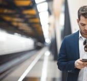 Mensagem texting do homem de negócios atrativo no telefone celular ao esperar o trem no metro foto de stock