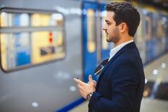 Mensagem texting do homem de negócios atrativo no telefone celular ao esperar o trem no metro fotografia de stock