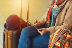 Mensagem texting do turista do moderno na tabuleta ou no modelo da tecnologia Viajante da pessoa que usa o computador no estação  imagem de stock royalty free