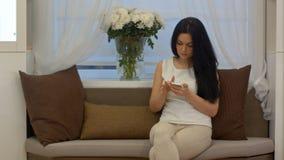 Mensagens de conversa e texting da mulher de negócios nova no telefone celular que senta-se no sofá em casa imagem de stock