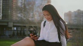 Mensagens de datilografia da estudante japonesa nova no telefone celular O cabelo da menina fundido - acima vídeos de arquivo