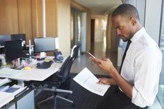 Mensagens de At Desk Checking do homem de negócios no telefone celular fotos de stock royalty free