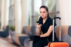 Mensagens de telefone da leitura da mulher na sala de espera do aeroporto fotos de stock royalty free