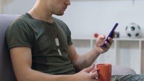 Mensagens do smartphone da leitura do sargento de exército que guardam o copo de café, descansando no sofá vídeos de arquivo