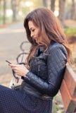 Mensagens texting fêmeas novas bonitos no telefone celular imagem de stock royalty free