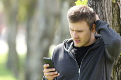Mensaje adolescente confuso de la lectura en un teléfono elegante Imagen de archivo libre de regalías