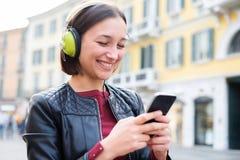 Mensaje al aire libre y que mecanografía de la música que escucha mp3 del estudiante feliz adentro Imagenes de archivo