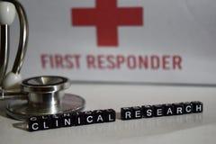 Mensaje clínico de la investigación escrito en bloques de madera Estetoscopio, concepto de la atención sanitaria fotos de archivo