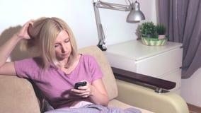 Mensaje de contestación del amigo de la mujer rubia joven en el uso social de la red, buscando para la información almacen de video