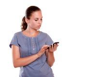 Mensaje de envío femenino bastante joven por el teléfono móvil Imagen de archivo