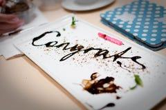 Mensaje de la enhorabuena escrito en chocolate en una fiesta de aniversario Imagenes de archivo