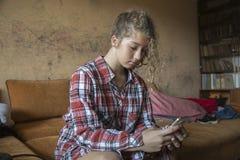 Mensaje de la escritura de la mujer del pelirrojo de la belleza de la chica joven en el teléfono celular Mirada abajo Imagen de archivo