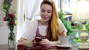 Mensaje de la escritura de la mujer en el teléfono móvil mientras que bebe té almacen de video