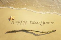 Mensaje de la Feliz Año Nuevo en la arena Fotos de archivo