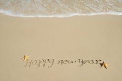 Mensaje de la Feliz Año Nuevo en la arena Imagenes de archivo