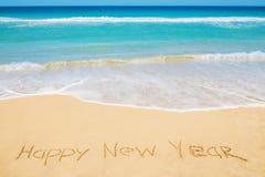 Mensaje de la Feliz Año Nuevo en la playa Foto de archivo libre de regalías