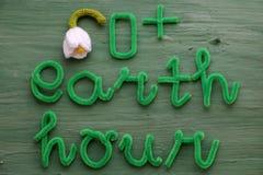 Mensaje de la hora de la tierra en fondo verde Imagen de archivo libre de regalías