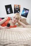 Mensaje de la lectura de la muchacha en el teléfono móvil en cama Imágenes de archivo libres de regalías