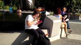 Mensaje de la lectura de la mujer al lado del agua de la fuente almacen de metraje de vídeo