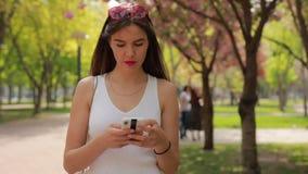 Mensaje de la lectura de la mujer en el smartphone que camina en el parque del verano almacen de video