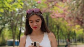 Mensaje de la lectura de la mujer en el smartphone que camina en el parque del verano metrajes