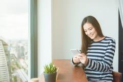 Mensaje de la lectura de la mujer en el teléfono móvil y sonrisas Foto de archivo libre de regalías