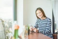 Mensaje de la lectura de la mujer en el teléfono móvil y sonrisas Fotos de archivo