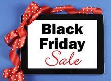 Mensaje de la venta de Black Friday en el dispositivo negro de la tableta del ordenador con la cinta roja Fotografía de archivo libre de regalías