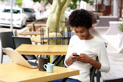 Mensaje de texto africano de la lectura de la mujer en el teléfono móvil en un café Imagen de archivo libre de regalías