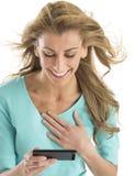 Mensaje de texto alegre de la lectura de la mujer Fotos de archivo libres de regalías