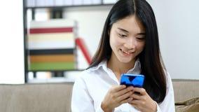 Mensaje de texto asiático de la lectura que juega de la mujer joven del retrato en el teléfono móvil en casa