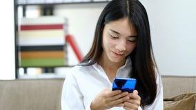 Mensaje de texto asi?tico de la lectura que juega de la mujer joven del retrato en el tel?fono m?vil en casa