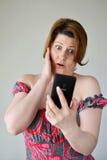 Mensaje de texto chocado de la lectura de la mujer joven Fotografía de archivo libre de regalías