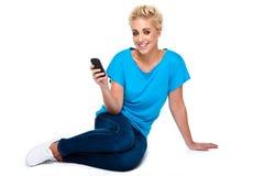 Mensaje de texto de la lectura de la mujer joven en el teléfono celular Imagen de archivo libre de regalías