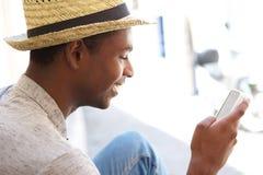 Mensaje de texto de la lectura del hombre joven en el teléfono celular Fotografía de archivo libre de regalías