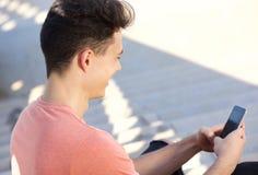 Mensaje de texto del individuo que mecanografía joven en el teléfono celular Fotos de archivo