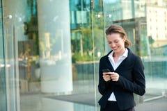 Mensaje de texto feliz de la lectura de la mujer de negocios en el teléfono móvil Foto de archivo libre de regalías