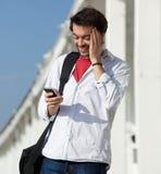 Mensaje de texto feliz de la lectura del hombre joven en el teléfono celular Imágenes de archivo libres de regalías