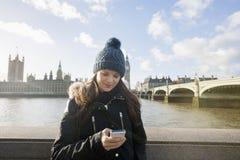 Mensaje de texto hermoso de la lectura de la mujer joven a través del teléfono elegante por el río Támesis, Londres, Reino Unido Foto de archivo