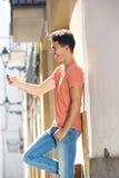 Mensaje de texto hermoso de la lectura del hombre joven en el teléfono celular Foto de archivo