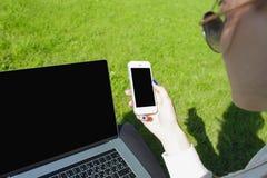 Mensaje de texto de la lectura del estudiante de mujer en el teléfono de célula, sentada en una hierba verde Imagenes de archivo